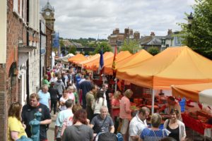 a busy high street market with bright orange sun shades over the stalls