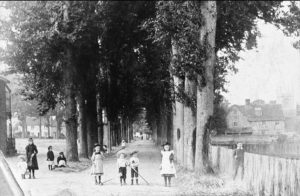 'The Mall', circa 1890, with children in typical dress of the time, stood beside mature trees, with the old Grammar School on right – with thanks to the Hungerford Virtual Museum