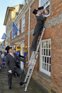 A Tutti Man climbs a ladder to steal a kiss from a Commoner on Tutti Day in Hungerford
