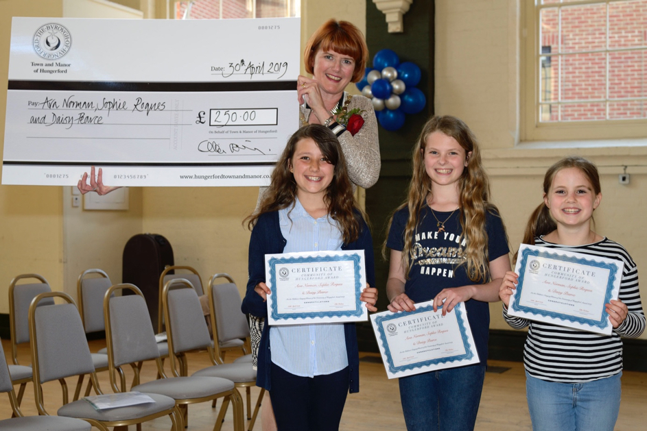 The winners of the first junior Hungerford Community Award is presented with a cheque by Town and Manor of Hungerford Constable Ellie Dickins